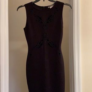Black bodycon dress with lace cutouts.